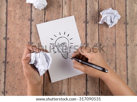Concept for a frustrated person having an idea and finding a solution. Person with crumpled paper and drawing a light bulb on a piece of paper on a wooden desk. - stock photo
