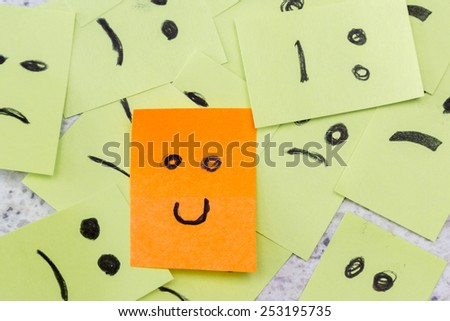 concept for a positive attitude with small office notes with multiple faces and one that stands out with a smile - stock photo