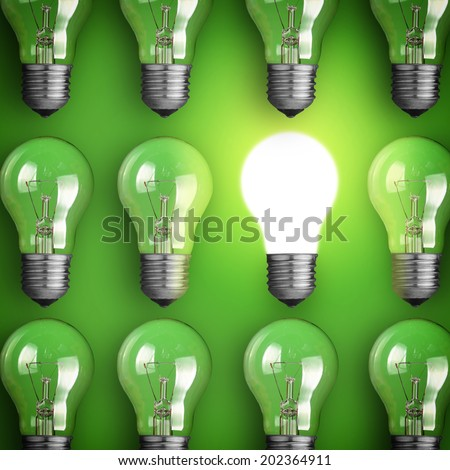 Concept for big idea. Glowing light bulb on green background - stock photo