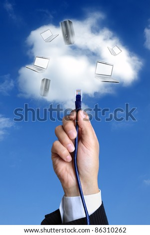 Concept for cloud computing -  busnessman hand connecting to the cloud with ethernet cable - stock photo