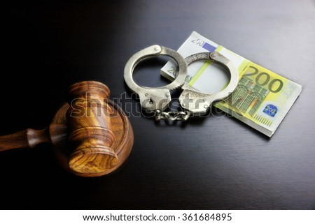 Concept For Corruption, Bankruptcy, Bail, Crime, Bribing, Fraud. Judges Gavel, Handcuffs   And Euro Cash On The Rough Black Wooden Textured Table Background. - stock photo