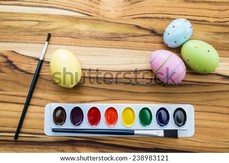 concept for easter eggs with pastel colors and paint brushes on a wooden table - stock photo