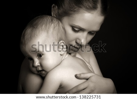 concept for love, family, and harmony. mother hugging baby tenderly in monochrome - stock photo