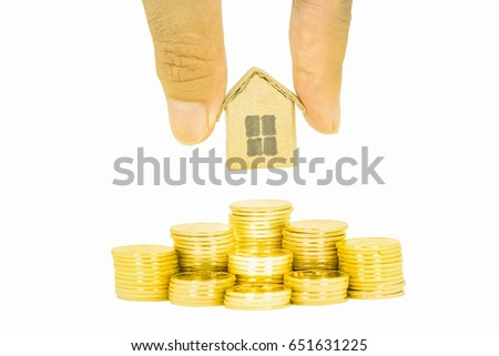 Concept for property ladder, mortgage and real estate investment. Man's hand putting house model on golden coins stacks. Isolated on white background.