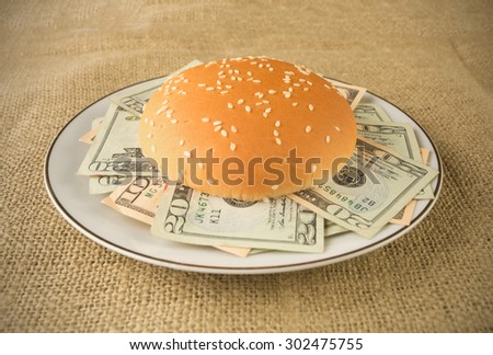 Concept for rich and greedy - Burger buns stuffed with money placed in a plate or a grunge table cloth - stock photo