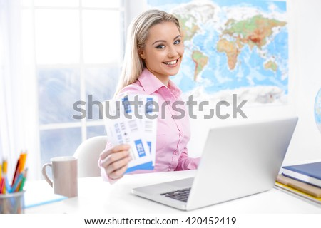 Concept for travel agent. Young blonde woman smiling, looking at camera and showing tickets. Travel agency office interior with big world map and window - stock photo