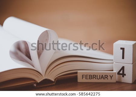 Concept for valentine or love - Open a book is placed on a heart-shaped books placed with calendar showing 14th of february in the backdrop wooden.