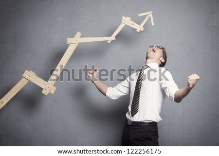 Concept: Great achievement in business. Enthusiastic young businessman cheering in front of business graph with positive trend, isolated on grey background. - stock photo