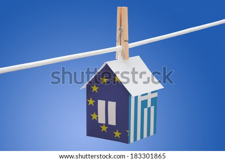 concept - Greece, Greek, and EU flag painted on a paper house hanging on a rope - stock photo