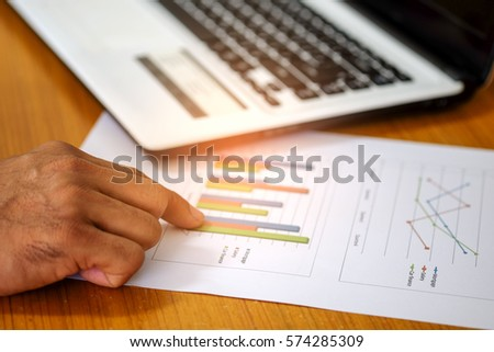 Concept,Hand on chart  with laptop computer.