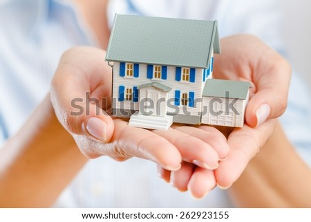 Concept. Hands presenting a small model of a house  - stock photo