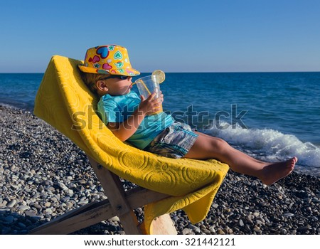 Concept holiday with kids - funny boy drinks juice lying in a deck chair on the beach