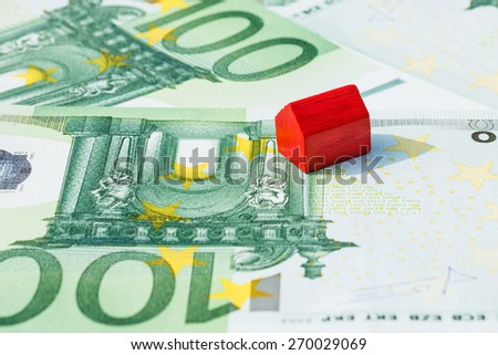 Concept house sell, foreclosure, debt, bill, mortgage on 100 euro banknotes. Focus on red house. - stock photo