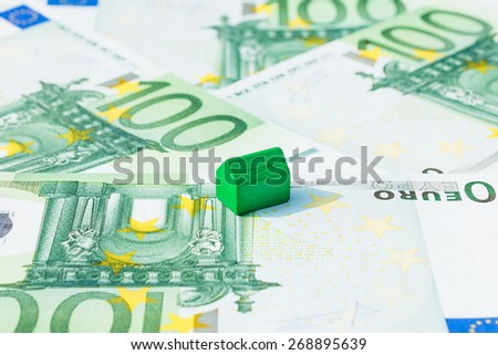 Concept house sell, pay bill, mortgage on hundred euro banknotes. Focus on green house. - stock photo