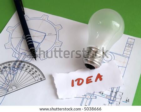 Concept 'idea': bulb, pencil on draft on green - stock photo