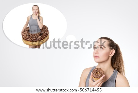 concept idea of a woman about to eat a donut but thinking she shouldn't really and it will not be good for the diet.