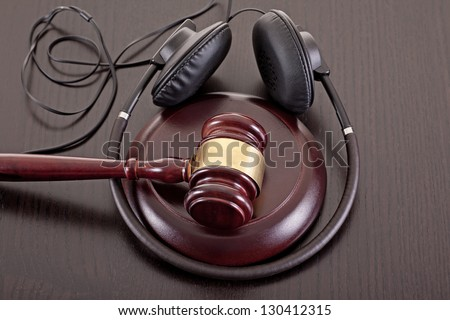 Concept image about music piracy and copyright protection law featuring  a gavel and headphones on tabletop - stock photo