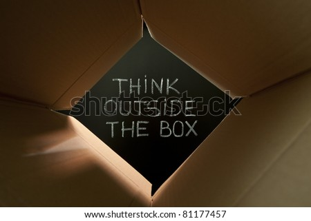 Concept image about unconventional or different thinking. Think outside the box handwritten with white chalk on blackboard. - stock photo