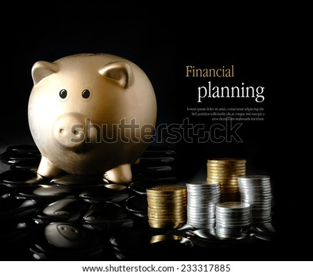 Concept image for financial planning. Creatively lit gold piggy bank and stacked coins against a black background. Copy space. - stock photo
