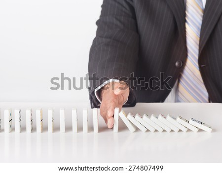 Concept image for solving problems. Image shows a business man wearing a black suit stopping falling dominoes. Image illustrates the concept of business strategy and solution to problems - stock photo