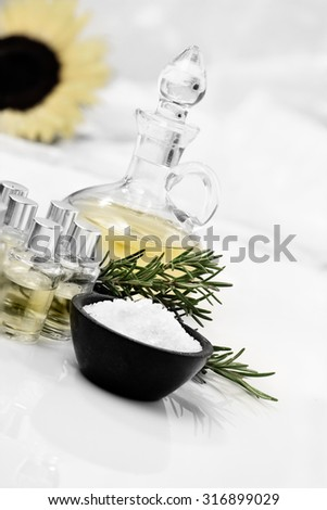 Concept image for spa, massage and healthy lifestyle. Essential oils and rosemary herbs with rock salt against a bright background. Copy space. - stock photo