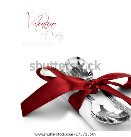 Concept image for Valentine dining or wedding breakfast.Two antique silver spoons on a pure white linen napkin with a burgundy red tie and bow against a white background. Copy space. - stock photo