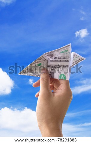 concept image Hand throwing the money paper airplane - stock photo