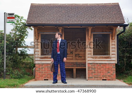 Concept image of a businessman standing at a bus stop having missed the last bus, in his rush to get ready he forgot to put his trousers on and is still wearing pyjama bottoms and slippers. - stock photo