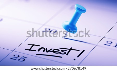 Concept image of a Calendar with a blue push pin. Closeup shot of a thumbtack attached. The words Invest written on a white notebook to remind you an important appointment. - stock photo