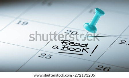 Concept image of a Calendar with a blue push pin. Closeup shot of a thumbtack attached. The words Read a book written on a white notebook to remind you an important appointment. - stock photo
