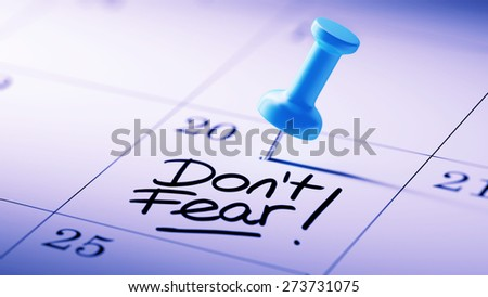 Concept image of a Calendar with a blue push pin. Closeup shot of a thumbtack attached. The words Don't Fear written on a white notebook to remind you an important appointment. - stock photo