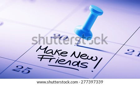Concept image of a Calendar with a blue push pin. Closeup shot of a thumbtack attached. The words Make new friends written on a white notebook to remind you an important appointment. - stock photo