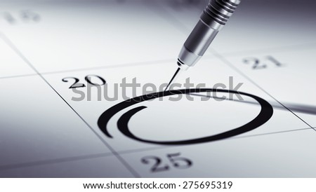 Concept image of a Calendar with a golden dart stick. Circle mark written on a white notebook to remind you an important appointment.