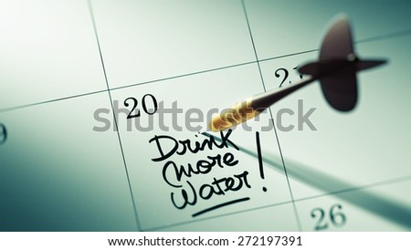 Concept image of a Calendar with a golden dart stick. The words Drink more water written on a white notebook to remind you an important appointment. - stock photo