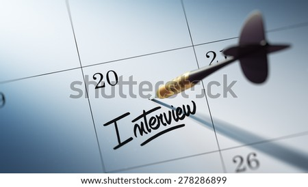 Concept image of a Calendar with a golden dart stick. The words Interview written on a white notebook to remind you an important appointment. - stock photo