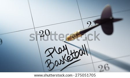 Concept image of a Calendar with a golden dart stick. The words Play Basketball written on a white notebook to remind you an important appointment. - stock photo