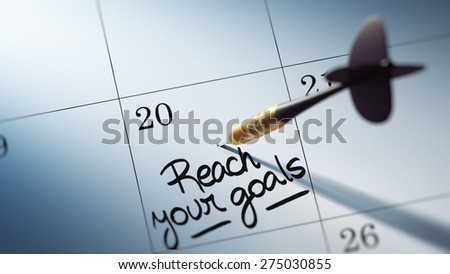 Concept image of a Calendar with a golden dart stick. The words Reach your goals written on a white notebook to remind you an important appointment. - stock photo