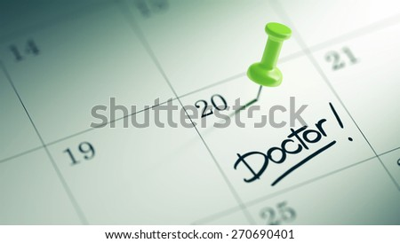Concept image of a Calendar with a green push pin. Closeup shot of a thumbtack attached. The words Doctor written on a white notebook to remind you an important appointment.
