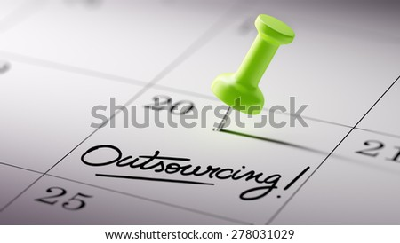 Concept image of a Calendar with a green push pin. Closeup shot of a thumbtack attached. The words Outsourcing written on a white notebook to remind you an important appointment. - stock photo
