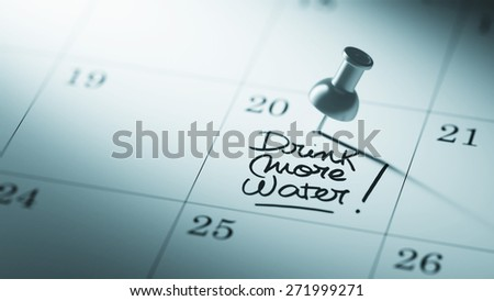 Concept image of a Calendar with a push pin. Closeup shot of a thumbtack attached. The words Drink more water written on a white notebook to remind you an important appointment. - stock photo