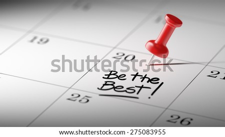Concept image of a Calendar with a red push pin. Closeup shot of a thumbtack attached. The words Be the best written on a white notebook to remind you an important appointment. - stock photo