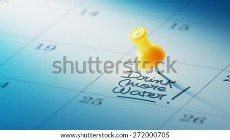 Concept image of a Calendar with a yellow push pin. Closeup shot of a thumbtack attached. The words Drink more water written on a white notebook to remind you an important appointment. - stock photo