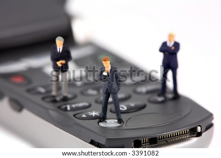 Concept image of a group of miniature businessmen standing on the keys of a cellphone. Focus is on the man in the center. - stock photo