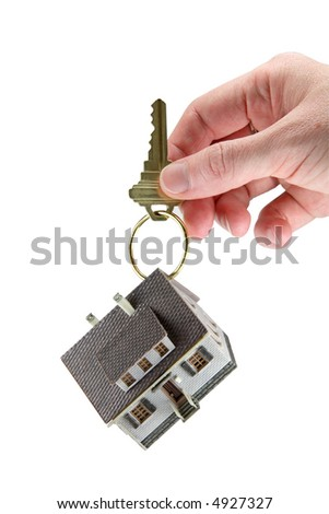 Concept image of a hand holding a house key with a miniature model house hanging from the key ring. White background.