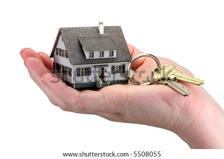 Concept image of a hand holding house keys. The miniature model house acts as a key ring with house keys hanging from it. White background. - stock photo