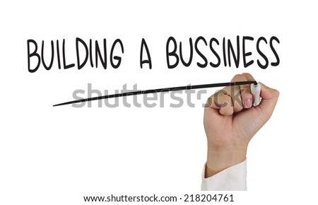 Concept image of a hand holding marker and write Building a Business words isolated on white - stock photo