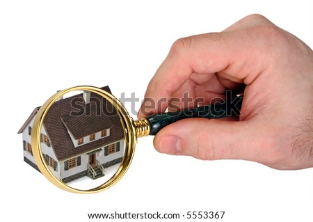 Concept image of a home inspection. A male hand holds a magnifying glass over a miniature house. White background