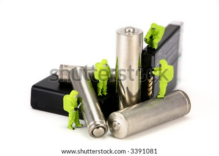 Concept image of a miniature HAZMAT team disposing of or recycling old batteries. Isolated on white background. - stock photo