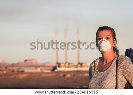 concept image of a woman wearing a mask and a walking stick walking away from a coal burning power plant with dirty smoke in the air - stock photo