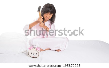 Concept image of an Irritated and sleepy young Asian girl destroying and alarm clock with a hammer